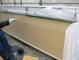 外壁の上塗り塗装をしている写真