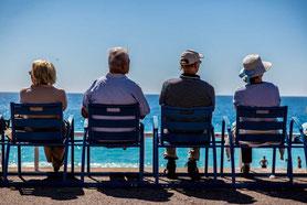 Rentner auf Bank vor Meer in Sonne, gemütlich mit privater Altersvorsorge
