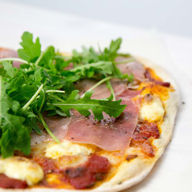 Pizza with prosciutto, rocket, cherry tomatoes and mascarpone.