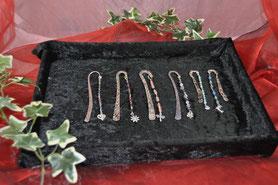 Das Bild zeigt Lesezeichen aus Tibet-Silber mit einer Perlenkette aus Halbedelsteinen oder Glas.