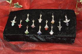 Das Bild zeigt Schutzengel aus Halbedelsteinen und Glas mit unterschiedlichen Tragemöglichkeiten, z.B. an Armband oder Halskette.