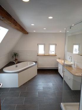 Bad im DG mit sichtbarem Deckenbalken, Eckbadewanne, Duschtasse mit Glastrennwand, großem Waschtisch, anthrazit Bodenfliesen, weiße Wandfliesen, 30 x 60 cm.