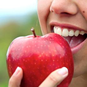 Nahaufnahme von Frau die in einen roten Apfel beißt.