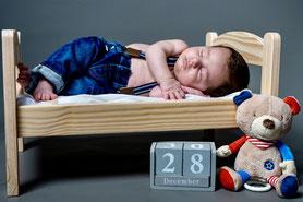 Kleiner Junge schläft während Neugeborenemfotoshooting in einem kleinen Puppenbett mit seinem Kuscheltier