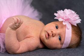 Baby mit Ballerina Kostüm guckt in die Kamera während Babyshooting