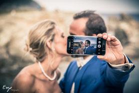 Photo de couple originale - mariés qui s'embrassent en selfie avec leur portable