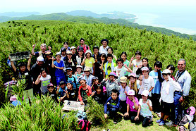 於茂登岳山頂で記念撮影する参加者一同=26日、午後