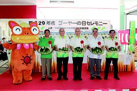 ゴーヤーを見せ消費拡大をPRする浦崎副知事(中央)や上原糸満市長(右から2人目)