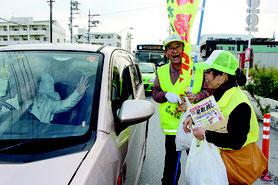 チラシとせんべいを配る参加者の笑顔につられ、ドライバーも笑顔になった=27日、安慶名十字路