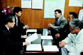 石垣島に軍事基地をつくらせない市民連絡会のメンバーや川原公民館の具志堅館長(右側中央)が漢那副市長(左側手前)に要請書を提出した=15日午前、市役所