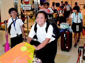 蘇澳鎮での交流事業を終えた児童生徒が帰島した。保護者や関係者に出迎えられて笑顔=3日、石垣空港