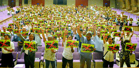 「基地」という文字にバツ印を入れた紙を掲げ、自衛隊配備反対を呼び掛ける参加者=22日夜、市民会館大ホール