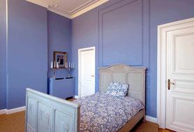Tapezierung und Wandanstrich mit Stuck-Dekoration im Schlafzimmer