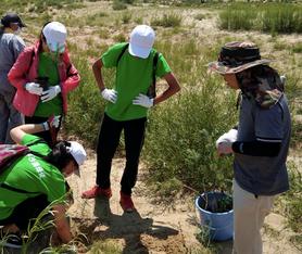 スタッフから植林方法を教えてもらいながら、苗木を植える生徒たち