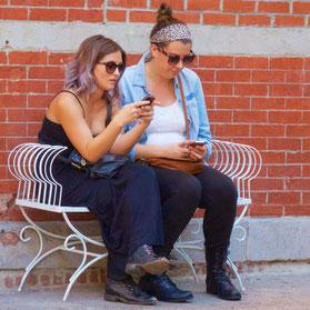 2-jeunes-femmes-assises-sur-un-banc-les-yeux-fixes-sur-leur-telephone-portable