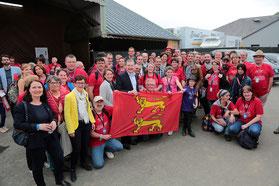 Les bénévoles et des élus de la Manche devant le drapeau normand
