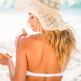 Frau im Bikini und Sonnenhut am Strand. Cremt sich mit Forever Sonnencreme ein.