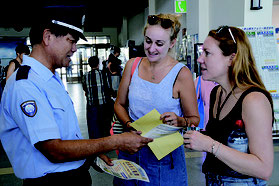 英語と中国語で外国人に注意を呼び掛けた上間支署長(左)=6日、離島ターミナル