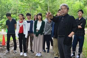 買収された赤井川村のキャンプ場でツアー参加者に解説する宮本編集委員(手前右)