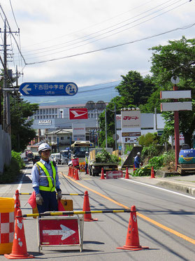 An jeder noch so kleinen Strassenbaustelle wird der Verkehr durch zwei Sicherheitsleute mit roten und weissen Fahnen geregelt.