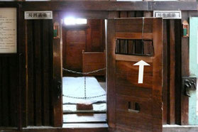 佐久間が脱獄したときの独房 監視員の覗き窓を枠(矢印)ごと外して逃げた。枠を堅く締め付けているネジ釘を味噌汁で腐食させて外したと言われている(HP博物館「網走監獄」より)