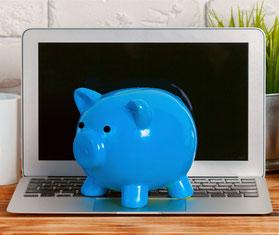 Laptop vor einer weißen Wand mit einem blauen Sparschwein