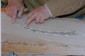 ④尾羽に接着剤を塗り、キリの地板にうめる。余分な接着剤をふき取る。