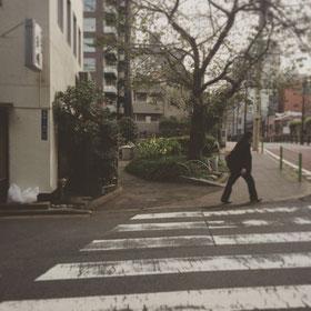 公園の端まで来て頂くと交差点にさしかかります。左手の天ぷら屋さんと写真中央の大きな木の間の小道にお進みください。