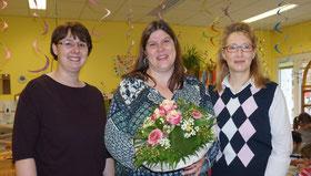 KiGa-Leiterin Tanja Kraus (links) und Simone Prell-Kaatz (rechts) vom Trägerverein gratulieren Corina Ortner-Heinrich