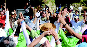 翁長知事を中心に、ガンバロー三唱をする参加者ら=10日、城岳公園