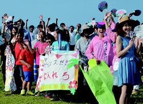 リハーサルで歓声をあげるギャラリーら。写真奥は参加男性=8日朝、南ぬ浜町緑地公園