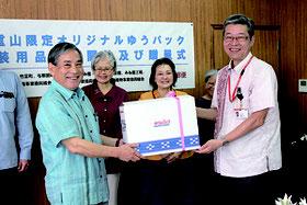 本間支所長(右)が「ゆうパック箱八重山版」を漢那副市長に贈呈した=20日、市役所庁議室