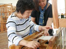 八重山上布のしおり作りを体験する古堅孝子さん(左)と教える上原久美さん=3日午前、石垣市伝統工芸館3階