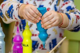 Petites mains sur un flacon bleu