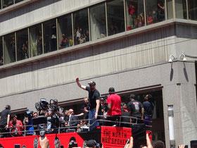 Toronto Raptors 2019: Bei der Parade durch die Innenstadt feiern Fans die Mannschaft. Man beachte  auch die Menschen in dem Bürogrbäude im Hintergrund.
