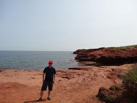 Selbstbildnis vor roter Steilküste im Prince Edward Island Nationalpark.