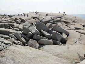 Touristen klettern auf den Felsen von Peggy's Cove.