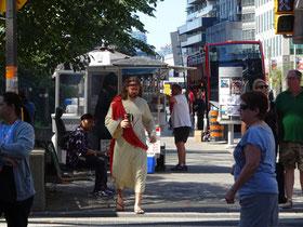 Ein Jesus-Darsteller läuft mit einem Kaffeebecher durch die Innenstadt von Toronto.