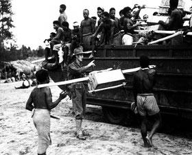 Aitape, Papua Neuguinea, August 1944. Auf Befehl weißer Offiziere mussten die Insulaner alles, was die kriegführenden Armeen brauchten, über glitschige Pfade ins umkämpfte Gebirge Neuguineas schleppen. (Quelle: National Archives, U.S. Army Signal Corps)