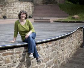 Daniela Wilhelm sitzt auf dem Rand einer Freilichtbühne