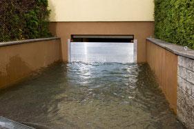 Bild zeigt eine überschwemmte Garagenabfahrt eines Einfamilienhauses mit montierten Dammbalken, an denen sich das Wasser wie geplant staut.