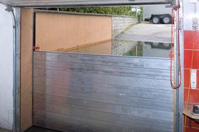 Bild zeigt den Blick aus der Garage eines Einfamilienhauses auf eine überschwemmte Garagenabfahrt mit montierten Dammbalken, an denen sich das Wasser wie geplant etwa 120cm hoch staut.