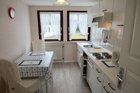Voll ausgestattete Küchenzeile  mit Sitzplatz für 2 Personen und großen Fenstern