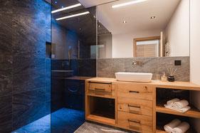 Badezimmer mit Walk-In Dusche in Stein- und Holzoptik
