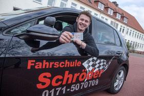 Das Foto zeigt einen jungen Mann, der in einem Auto der Schroeder Fahrschule sitzt, sich aus dem Fenster lehnt und glücklich seinen Führerschein zur Kamera hält.