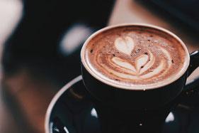 Cappuccino in schwarzer Tasse