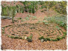 Labyrinth aus Steinen in Herbstlaub für ein Ritual der Achtsamkeit