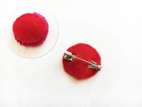 一回り小さい丸のフェルトを用意し、真ん中に切り込みを入れ、ピンを入れ込みボンドで固定