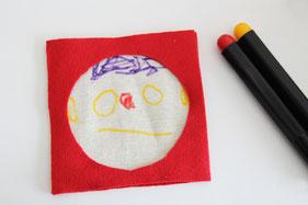 無地布にペンでお絵描きまたは刺繍などで装飾します。
