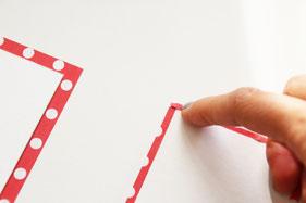 折り紙にのりをつけ厚紙をつつみます。